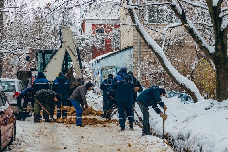 Groupe de travailleurs de la construction méconnaissables réparant les câbles ou la canalisation souterrains de communication photos stock