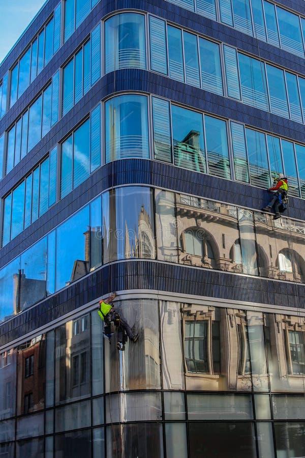 Groupe de travailleurs nettoyant le service de fenêtres sur le bâtiment ayant beaucoup d'étages photographie stock