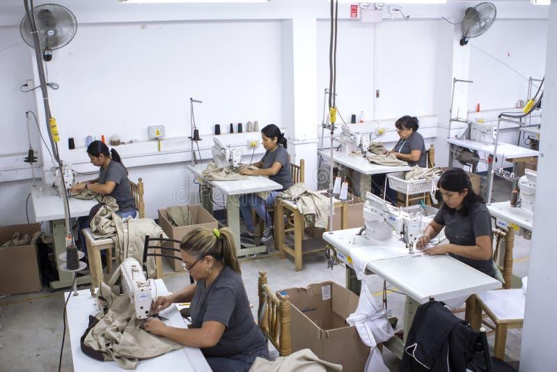 Groupe de travailleurs péruviens avec la machine à coudre apportant des changements aux vêtements photos stock