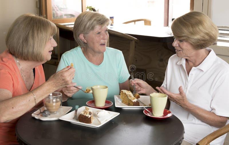 Groupe de trois amies mûres supérieures de femmes de beau Moyen Âge se réunissant pour le café et le thé avec des gâteaux au café photographie stock
