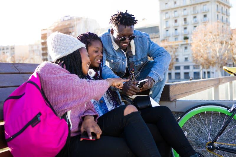Groupe de trois amis à l'aide du téléphone portable dans la rue photo libre de droits