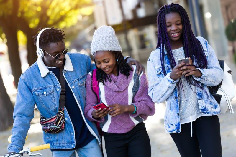 Groupe de trois amis à l'aide du téléphone portable dans la rue photos stock