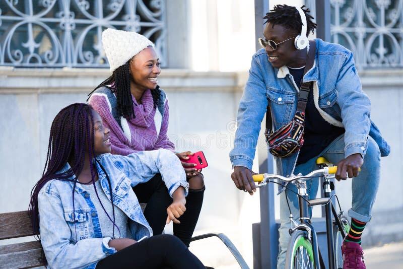 Groupe de trois amis parlant dans la rue photos stock