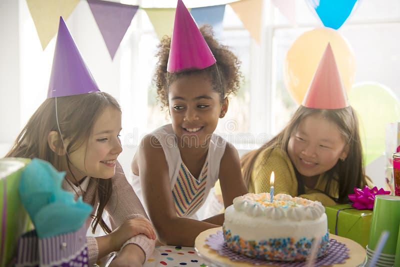 Groupe de trois enfants adorables ayant l'amusement à la fête d'anniversaire image libre de droits