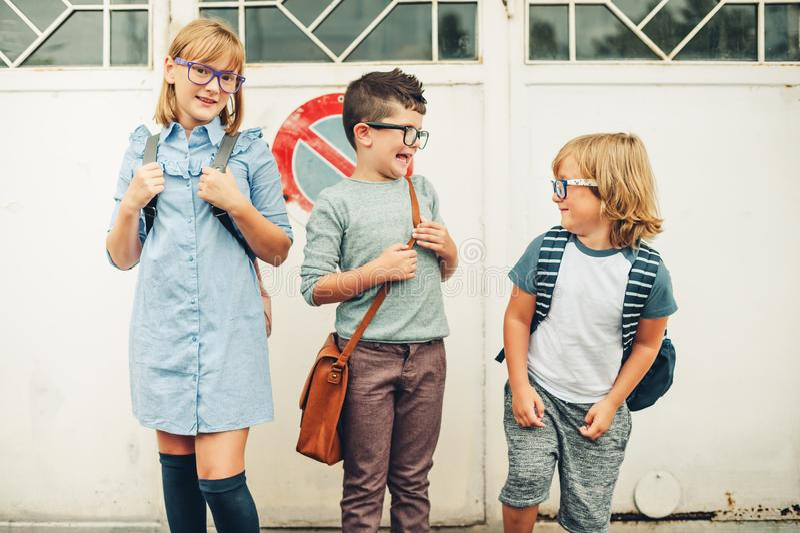 Groupe de trois enfants drôles utilisant des sacs à dos marchant de nouveau à l'école photo stock