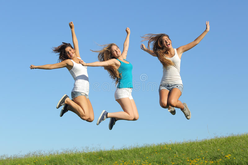 Groupe de trois filles d'adolescent sautant sur l'herbe image stock