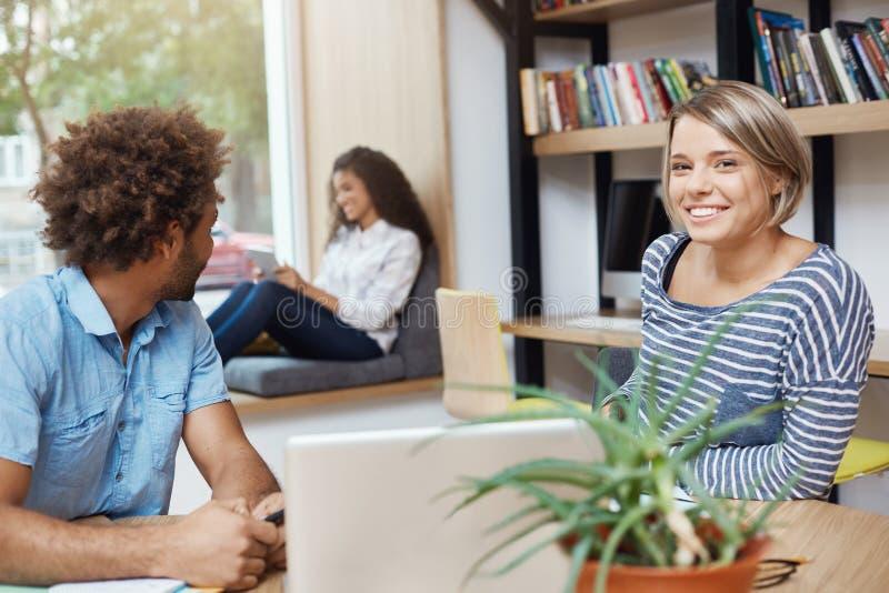 Groupe de trois jeunes étudiants multi-ethniques beaux s'asseyant à la bibliothèque universitaire Type à la peau foncée regardant photographie stock