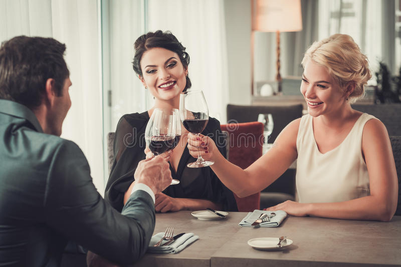 Groupe de verres tintants de personnes riches de vin rouge dans le restaurant photos stock