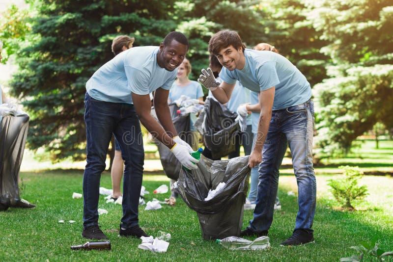 Groupe de volontaires avec des sacs de déchets nettoyant le parc photographie stock libre de droits