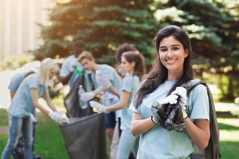 Groupe de volontaires avec des sacs de déchets nettoyant le parc image stock