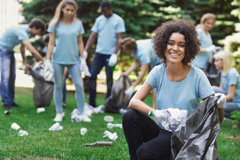 Groupe de volontaires avec des sacs de déchets nettoyant le parc photographie stock