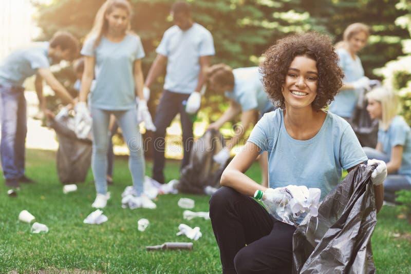 Groupe de volontaires avec des sacs de déchets nettoyant le parc images stock