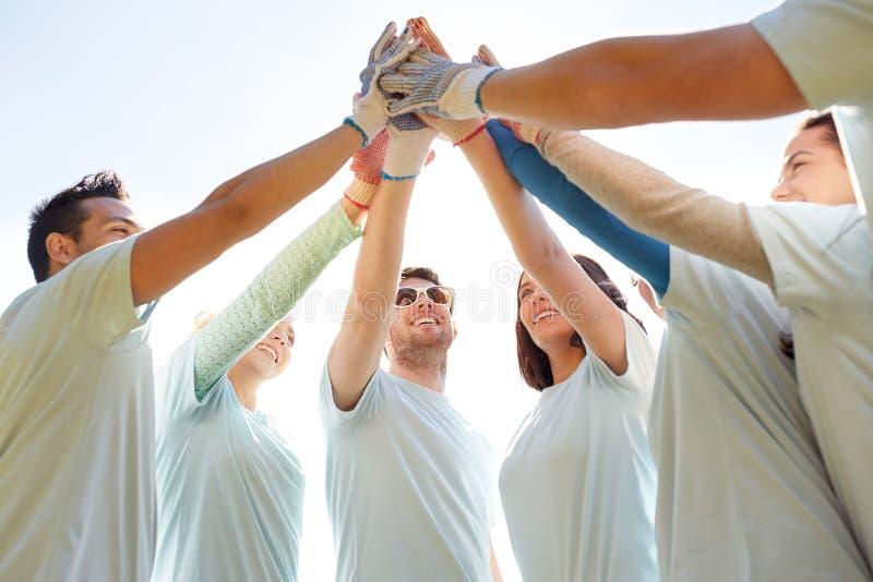 Groupe de volontaires faisant la haute cinq dehors image stock