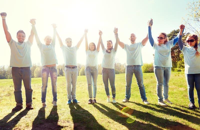 Groupe de volontaires heureux tenant des mains dehors photos stock