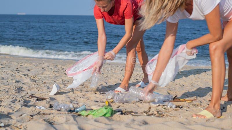 Groupe de volontaires nettoyant la ligne de plage Les gens rangeant des déchets sur le bord de mer Concept d'?cologie image stock
