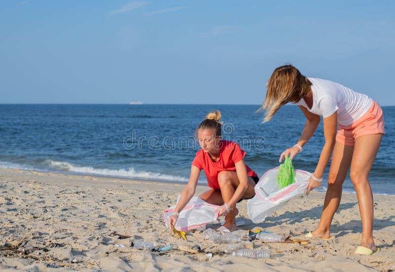 Groupe de volontaires nettoyant la ligne de plage Les gens rangeant des déchets sur le bord de mer Concept d'?cologie photographie stock libre de droits