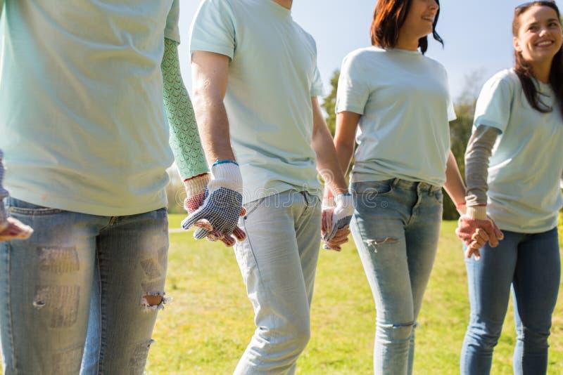 Groupe de volontaires tenant des mains en parc photographie stock libre de droits