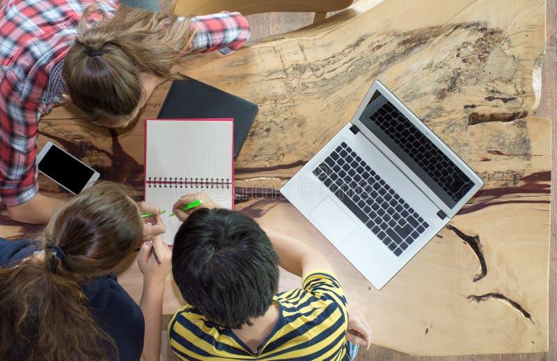 Groupe de vue supérieure d'amis adolescents travaillant dans l'équipe avec des rapports et l'ordinateur portable sur la table en  photo libre de droits