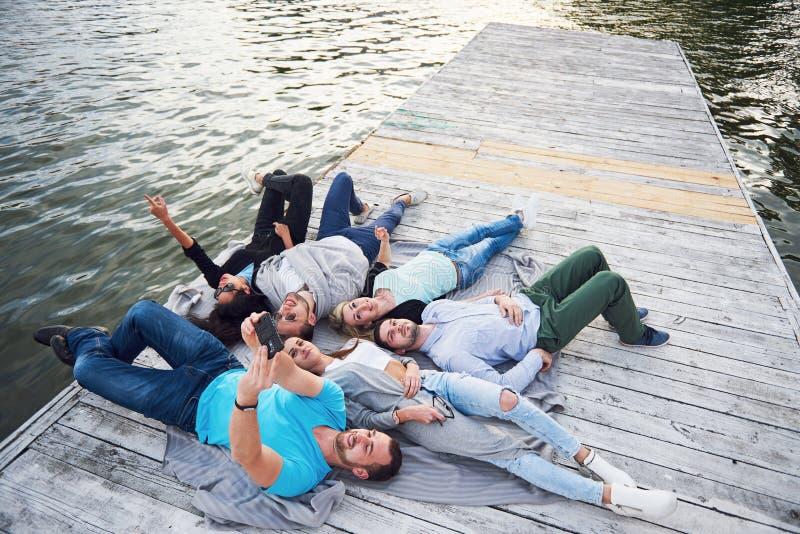 Groupe des beaux jeunes qui font Selfies se trouvant sur le pilier, les meilleurs amis des filles et des garçons avec plaisir photos libres de droits
