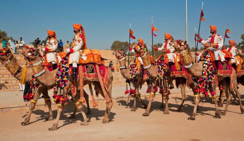 Groupe des cavaliers de chameau dans des uniformes allant au festival de désert photographie stock