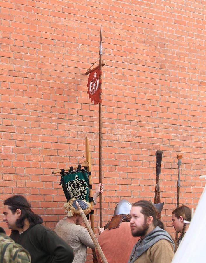 Groupe des hommes dans les costumes des soldats antiques près d'un mur de briques rouge photographie stock libre de droits