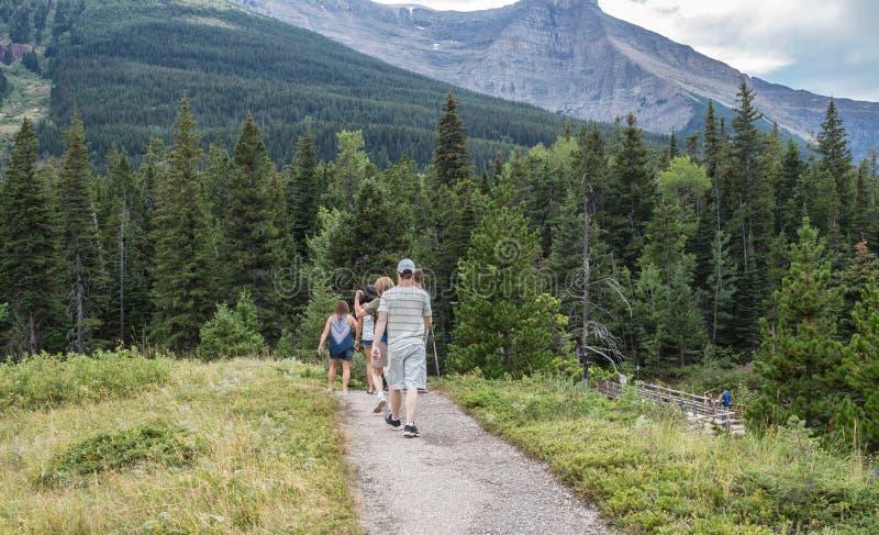 Groupe des hommes et de femmes trimardant dans les montagnes image stock