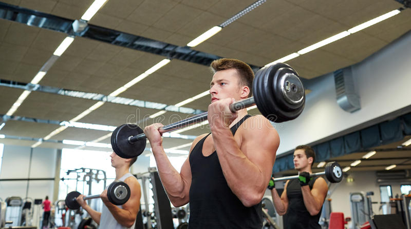 Groupe des hommes fléchissant des muscles avec le barbell dans le gymnase photographie stock libre de droits