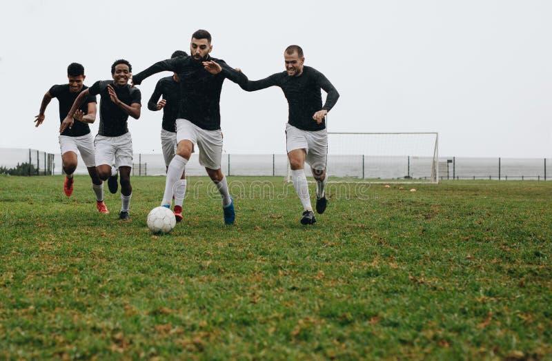Groupe des hommes jouant au football sur le champ image libre de droits
