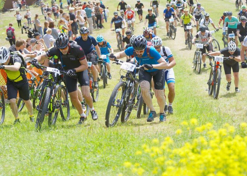 Groupe des hommes menant son vélo de montagne vers le haut, behin de concurrents photo libre de droits