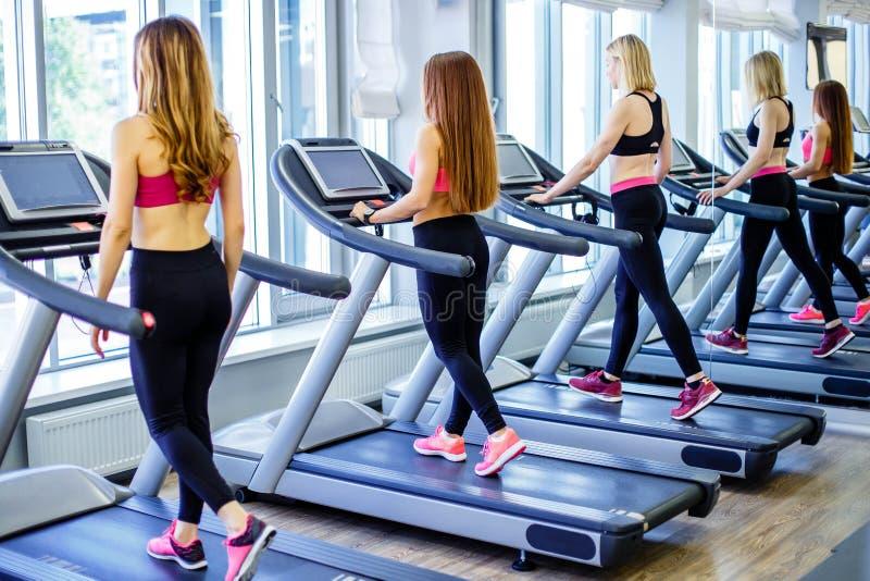 Groupe des jeunes à l'aide des tapis roulants à un centre de fitness photographie stock libre de droits