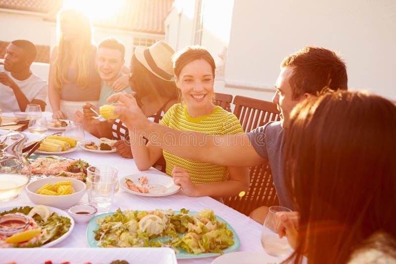 Groupe des jeunes appréciant le repas extérieur d'été images stock