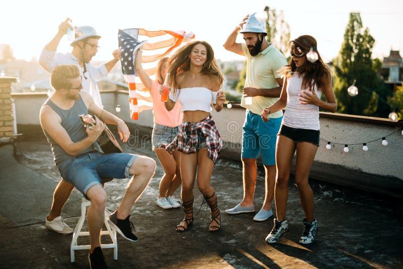 Groupe des jeunes ayant l'amusement à une partie d'été, au coucher du soleil image stock