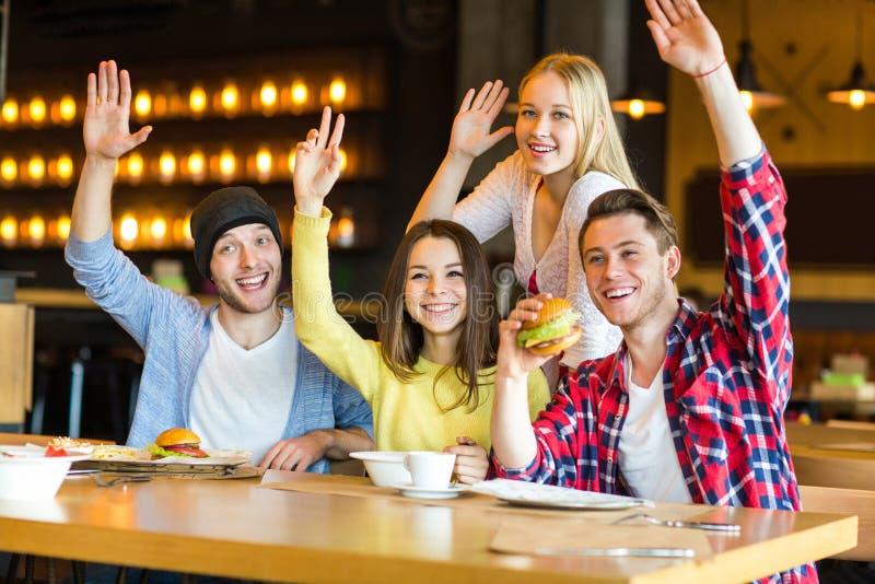 Groupe des jeunes ayant l'amusement en café image libre de droits