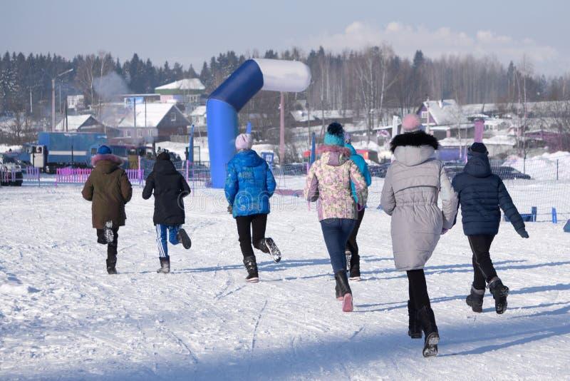 Groupe des jeunes dans les vêtements de sport encourageant la ligne d'arrivée de croisement de jeune homme sportif en parc neigeu image libre de droits