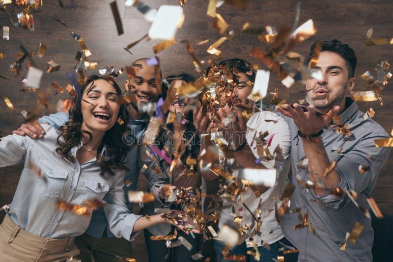 Groupe des jeunes gais se tenant ensemble et célébrant avec des confettis image stock