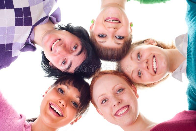 Groupe des jeunes heureux en cercle image stock