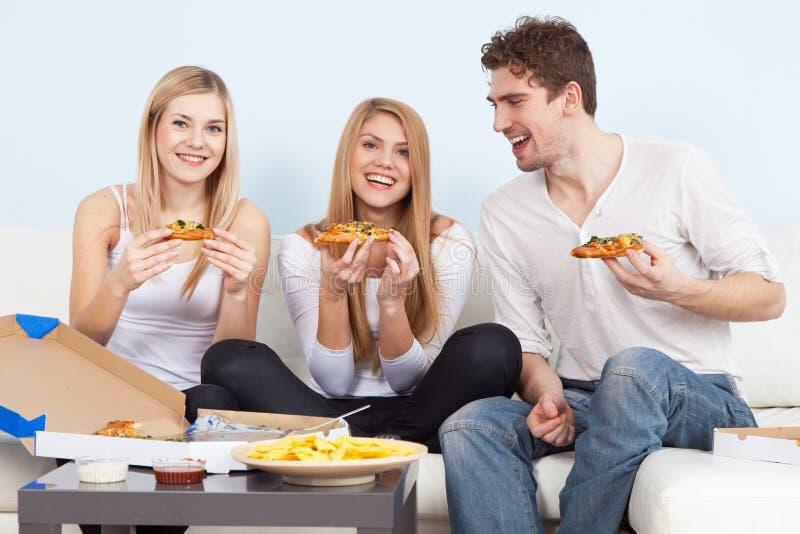Groupe des jeunes mangeant de la pizza à la maison photo libre de droits
