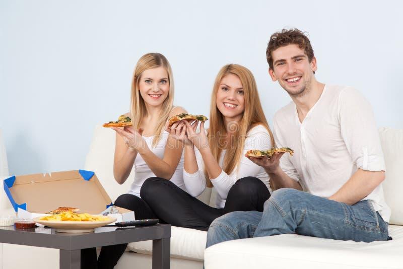 Groupe des jeunes mangeant de la pizza à la maison photos libres de droits