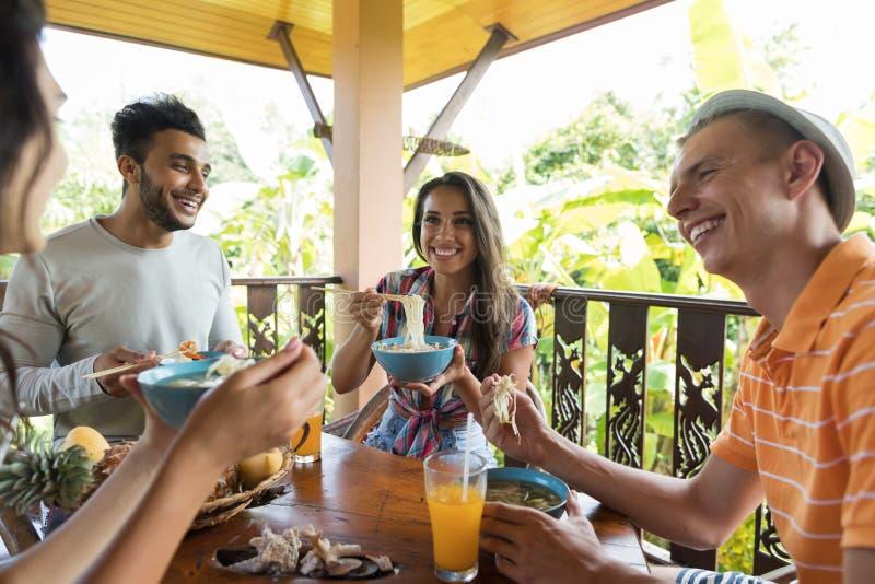 Groupe des jeunes parlant tout en mangeant les amis asiatiques traditionnels de nourriture de soupe de nouilles dinant ensemble images libres de droits