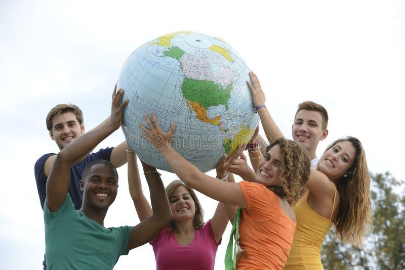 Groupe des jeunes retenant une terre de globe images stock