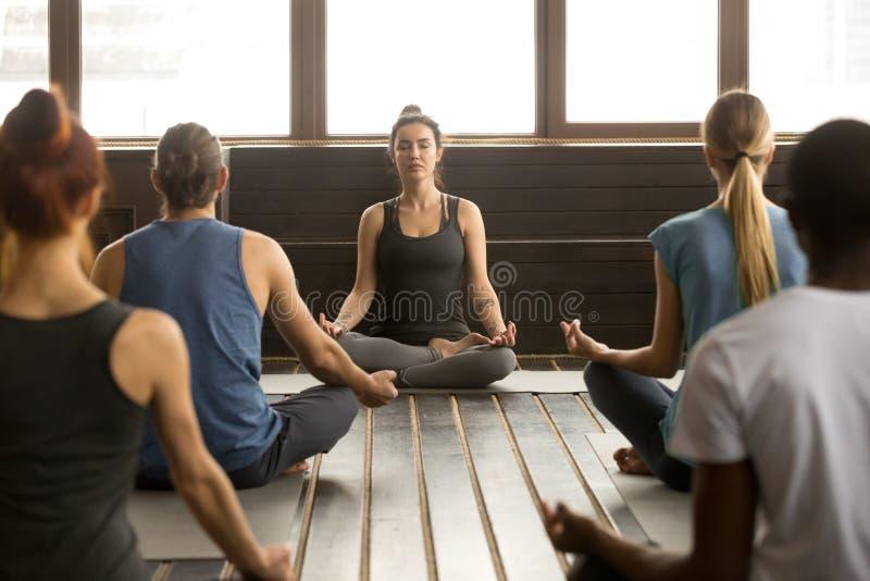 Groupe des jeunes s'asseyant dans Sukhasana images libres de droits