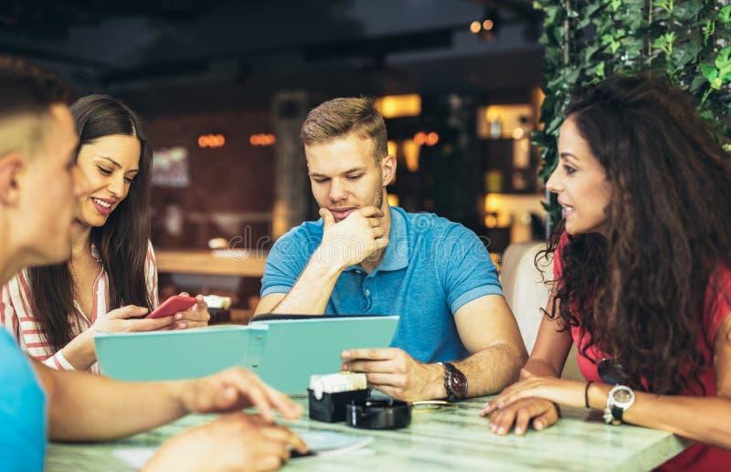 Groupe des jeunes se réunissant dans un café image stock