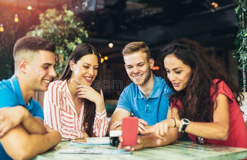 Groupe des jeunes se réunissant dans un café photo libre de droits