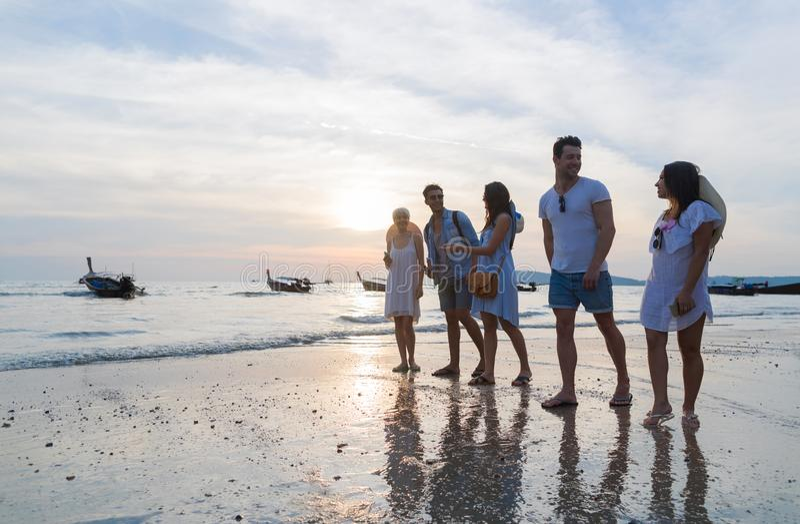 Groupe des jeunes sur la plage aux vacances d'été de coucher du soleil, bord de la mer de marche d'amis photo libre de droits
