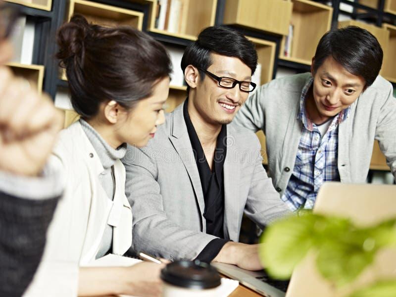 Groupe des jeunes travaillant dans le bureau image stock