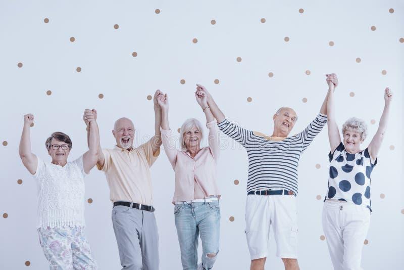 Groupe des personnes âgées actives jugeant des mains hautes et appréciant le mee photos libres de droits
