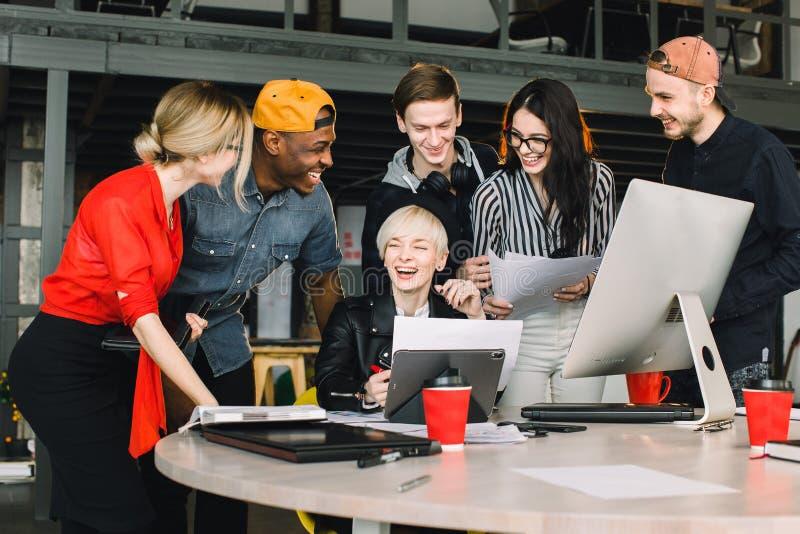 Groupe divers d'hommes d'affaires se réunissant ensemble au bureau moderne Femme dans le chapeau noir montrant son travail à l'in photos libres de droits