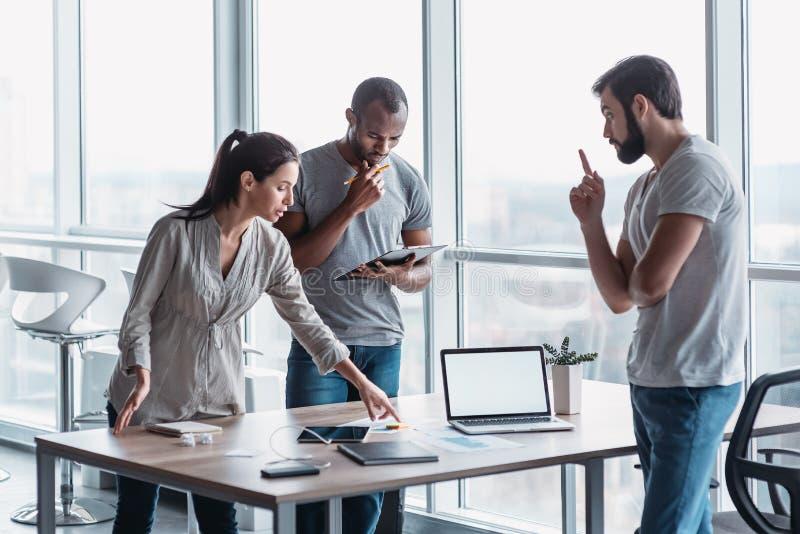 Groupe divers de collègues focalisés discutant la stratégie commerciale ensemble au cours d'une réunion dans un bureau images libres de droits
