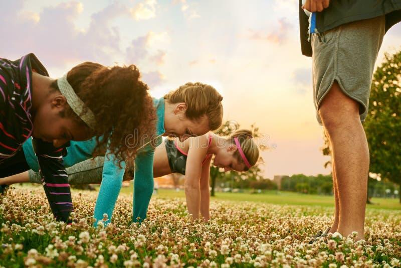 Groupe divers de femmes pendant une formation de forme physique faisant des pousées au coucher du soleil en parc naturel images libres de droits