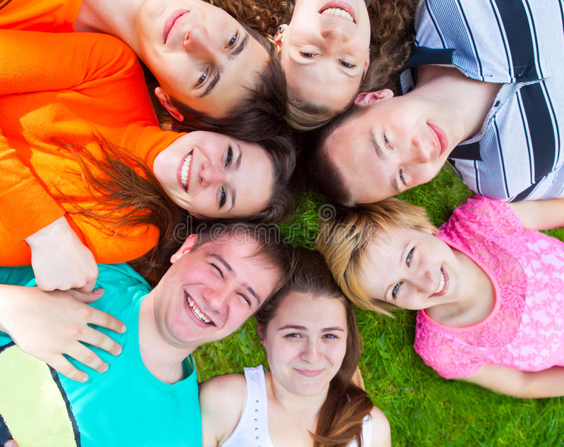 Groupe divers de mensonge extérieur d'amis sur une pelouse photo stock